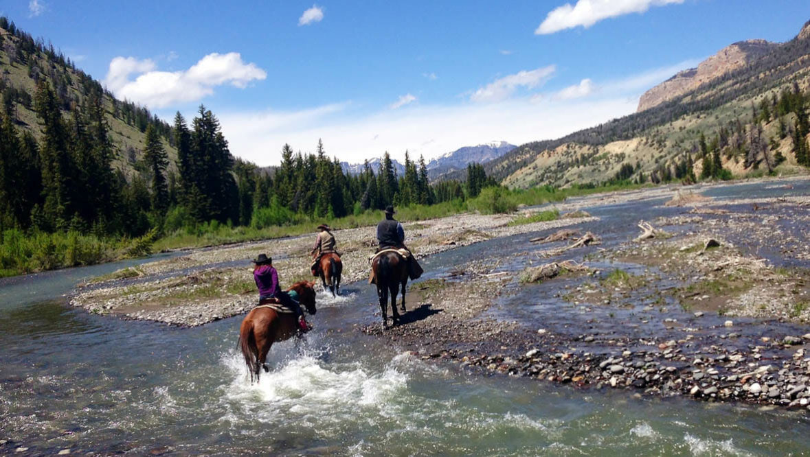 Riders crossing a creek at Lazy L&B Ranch