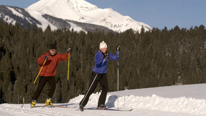 Two guests cross country skiing at Lone Mountain Ranch