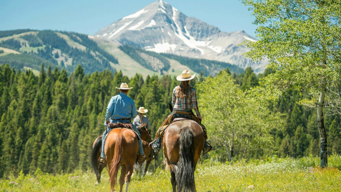 Two guests on horses looking at the mountains at Lone Mountain Ranch