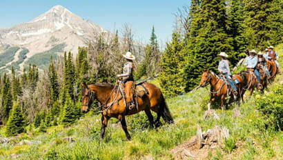 A family riding horses on the Lone Mountain trail
