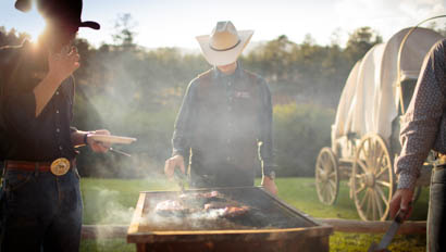Cowboy grilling food outside at Lost Valley Ranch