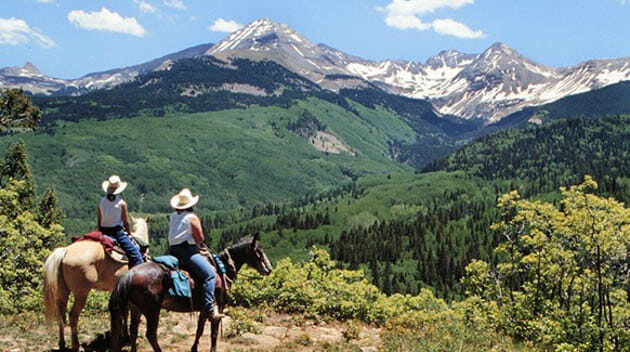 Two people on horseback looking at the mountain view