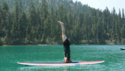 Guest doing a headstand on a paddle board on a lake at McGinnis Meadows Cattle Ranch
