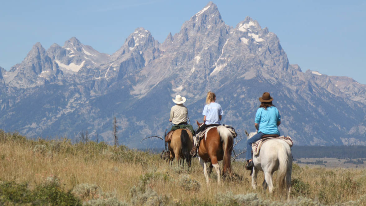 Trail ride with the Grand Tetons in the background at Moosehead Ranch