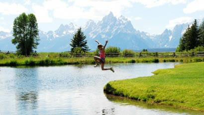 Kid jumping into a river at Moosehead Ranch