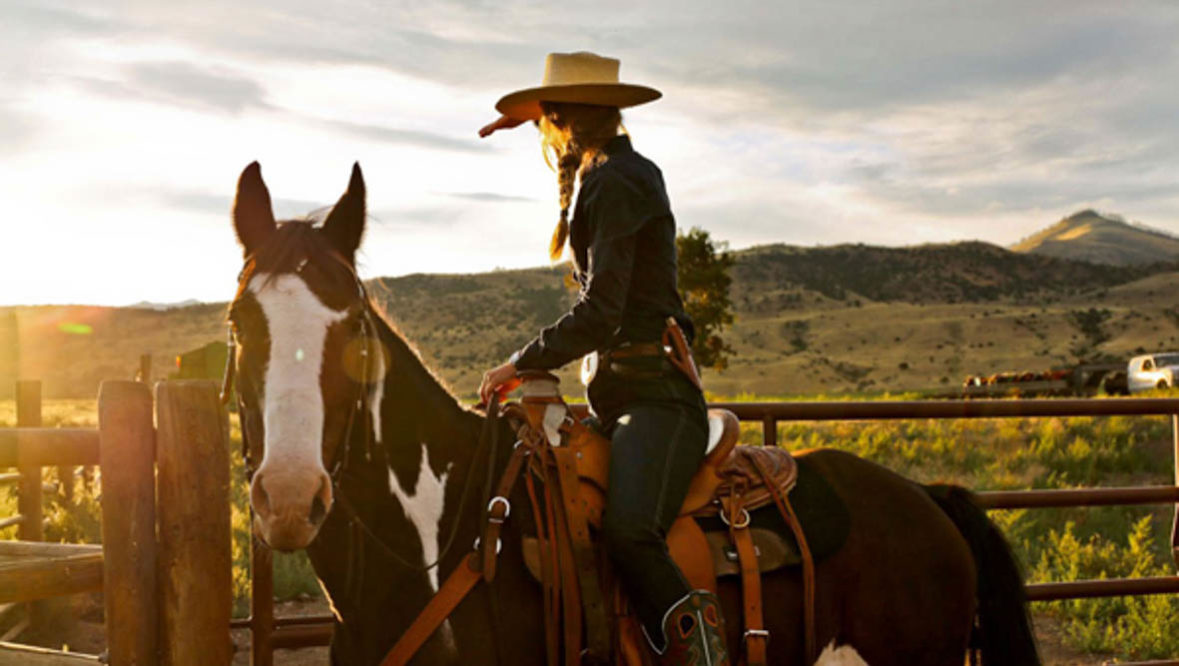 Cowgirl on a horse at sunset at Mountain Sky Guest Ranch