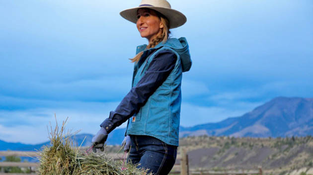 Woman in cowboy hat and jacket carrying a bale of hay