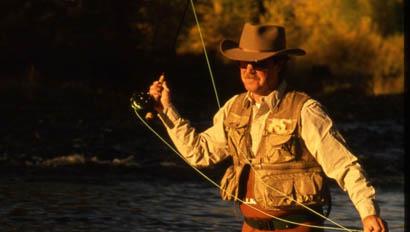 Man fly fishing in a river at Nine Quarter Circle Ranch