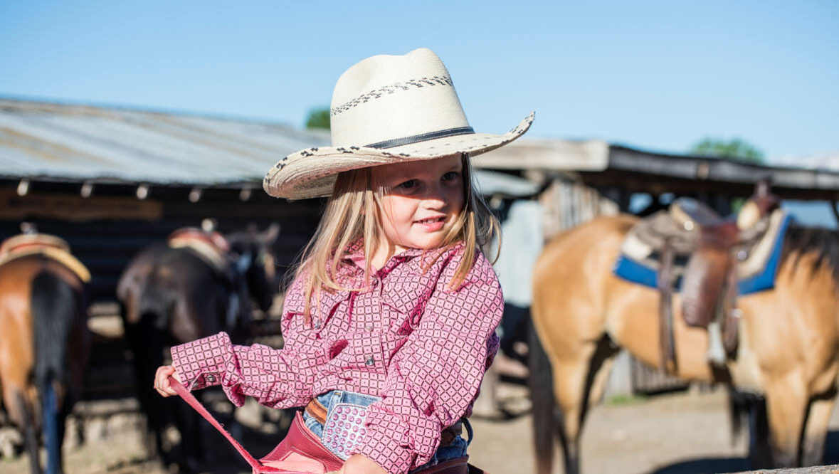Little girl with cowboy hat on a horse at Parade Rest Ranch