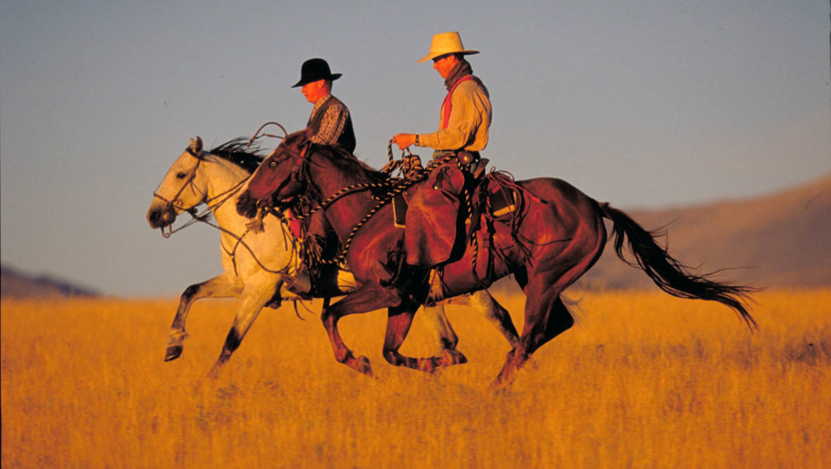 Two riders on a trail loping at Paradise Guest Ranch