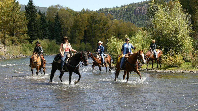 Trail ride through a river at Rainbow Trout Ranch