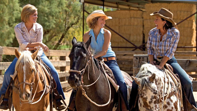 Three cowgirls riding horses at Rancho de los Caballeros