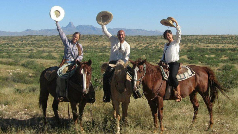 Three riders waving their cowboy hats at Rancho de la Osa