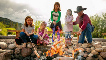 Group of kids roasting hot dogs over a camp fire at Rawah Ranch