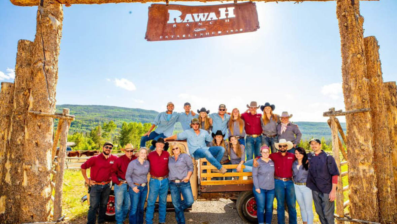 Rawah Ranch crew standing under the Rawah Ranch sign
