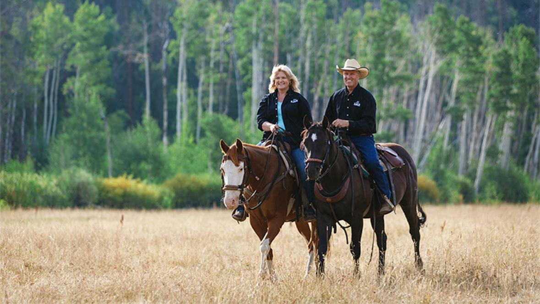 A couple horseback riding at Rawah Ranch