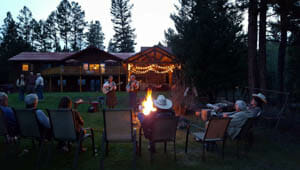 Guests dining around camp fire at Rich's Montana Guest Ranch