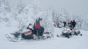 Guests snowmobiling on a snowy trail at Rich's Montana Guest Ranch