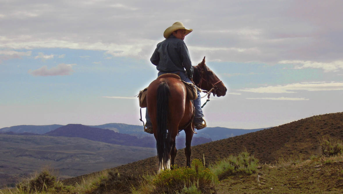 Teenager on a horse looking at an amazing view at Rimrock Dude Ranch