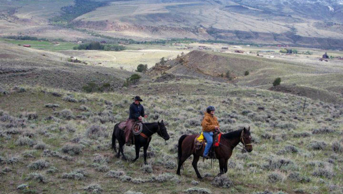 Two riders on a trail with a view at Rimrock Dude Ranch