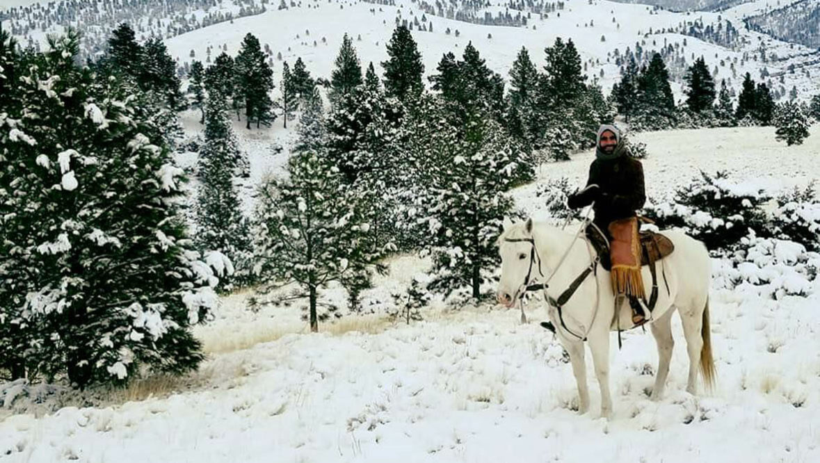 Man on horse in the snow at Rocking Z Ranch