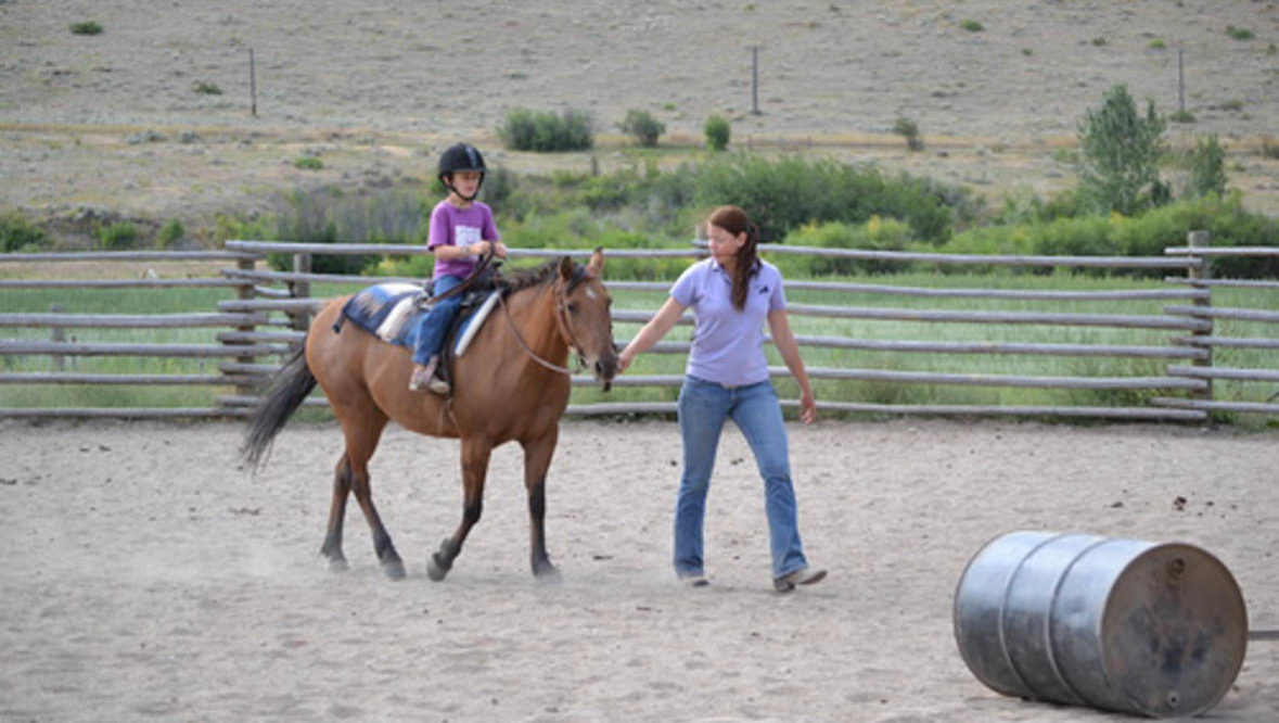Instructor leading a child on a horse in an arena at Rocking Z Ranch
