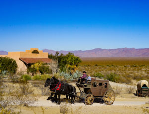Stagecoach wagon being pulled by two horses with Mountains in background