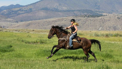 Sundance Guest Ranch person galloping on a horse through a field