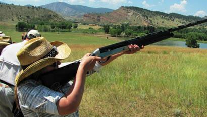 Sylvan Dale Ranch woman shooting a rifle