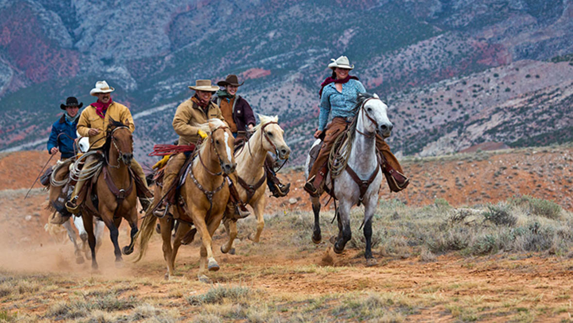 Group of riders loping at Hideout Lodge Ranch