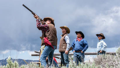 Three men watching one man shoot a rifle at Triangle C Ranch