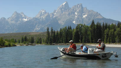 Two people in a boat fishing on a lake at Triangle X Ranch