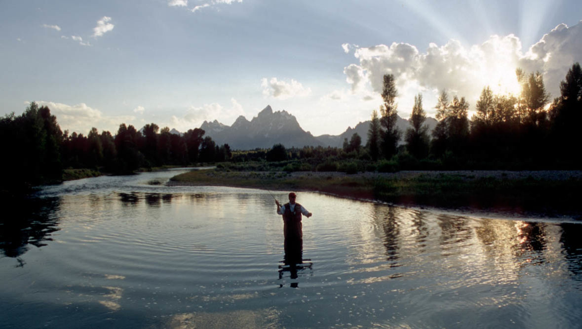 Man fishing in a lake at Triangle X Ranch
