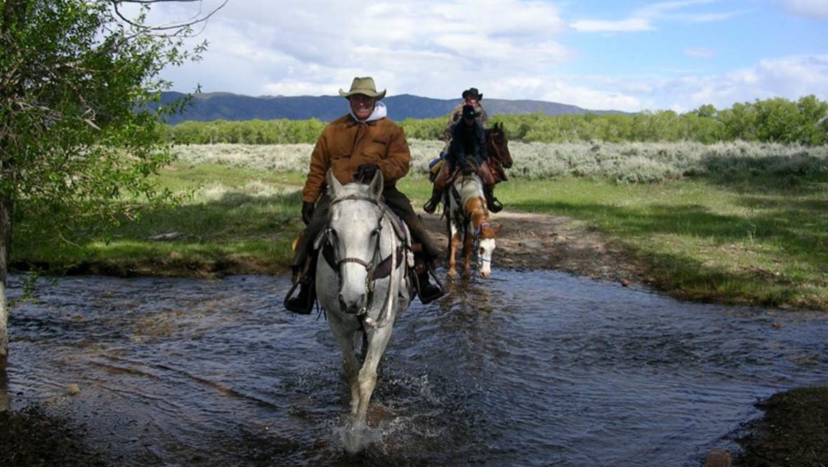 Two people on horses crossing a creek at Vee Bar Ranch