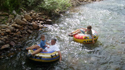 Kids and dad floating down a creek on tubes at Vee Bar Ranch