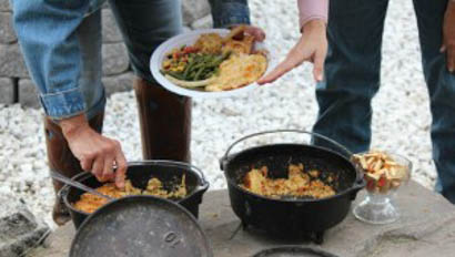 People serving food out of cast iron pots