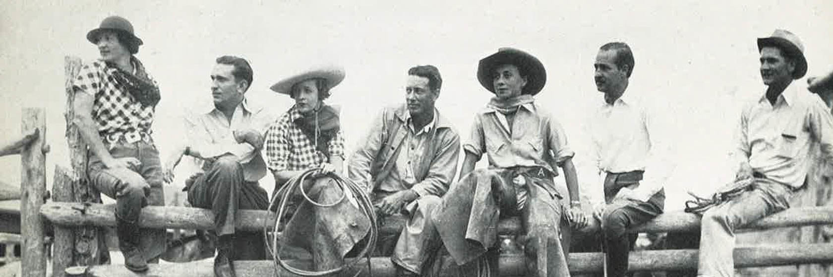 Old photo of guests in cowboy gear sitting on a fence
