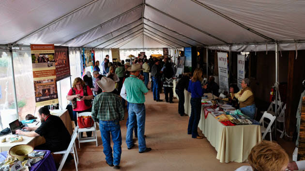 People walking around under an event tent with vendors at tables