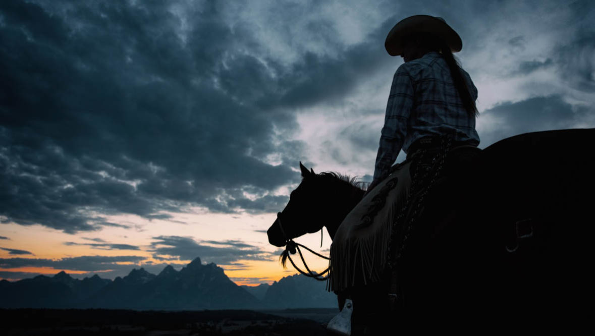 Cowgirl on a horse at dawn watching the sun rise at Lost Creek Ranch