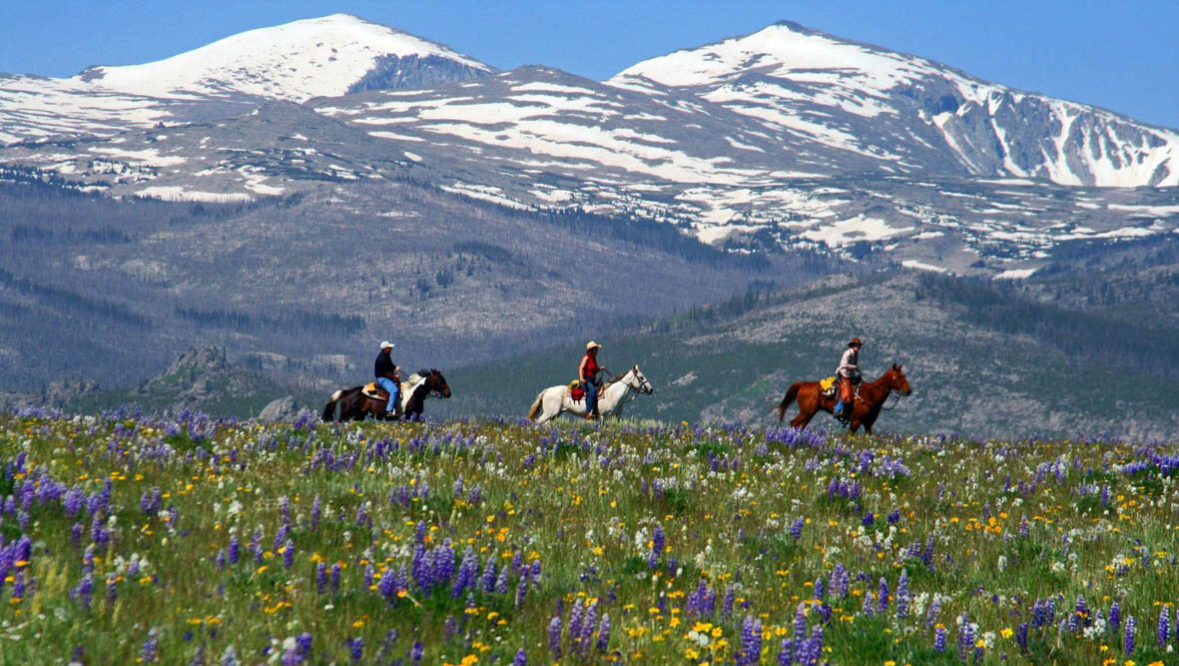 Trail ride with mountains in the background at Paradise Guest Ranch
