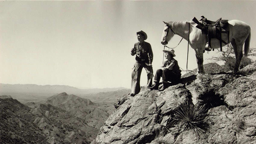 Old photo of a horse and two people on a rock