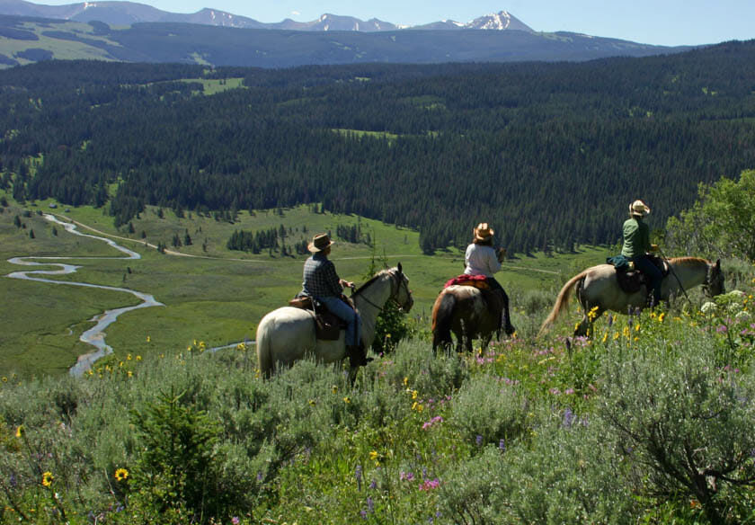 Three people riding horses on a trail overlooking a valley