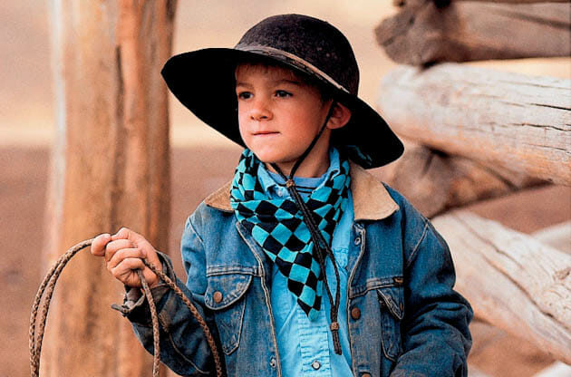 Young cowboy with a hat and lasso
