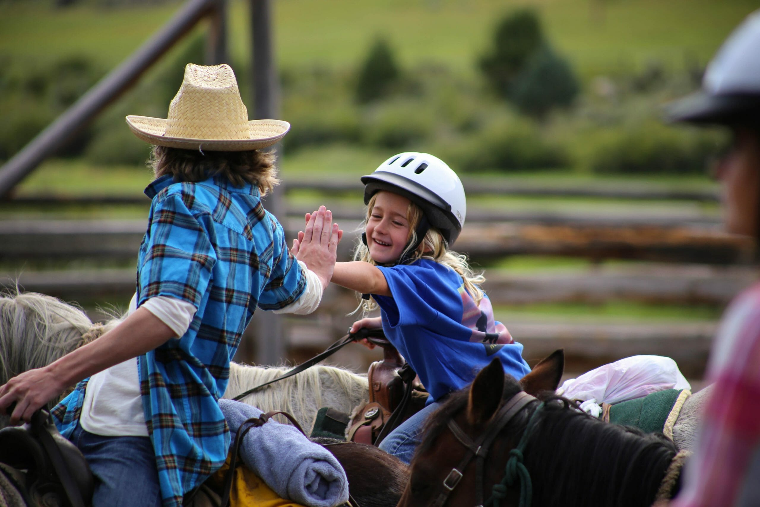 kids high fiving at a dude ranch