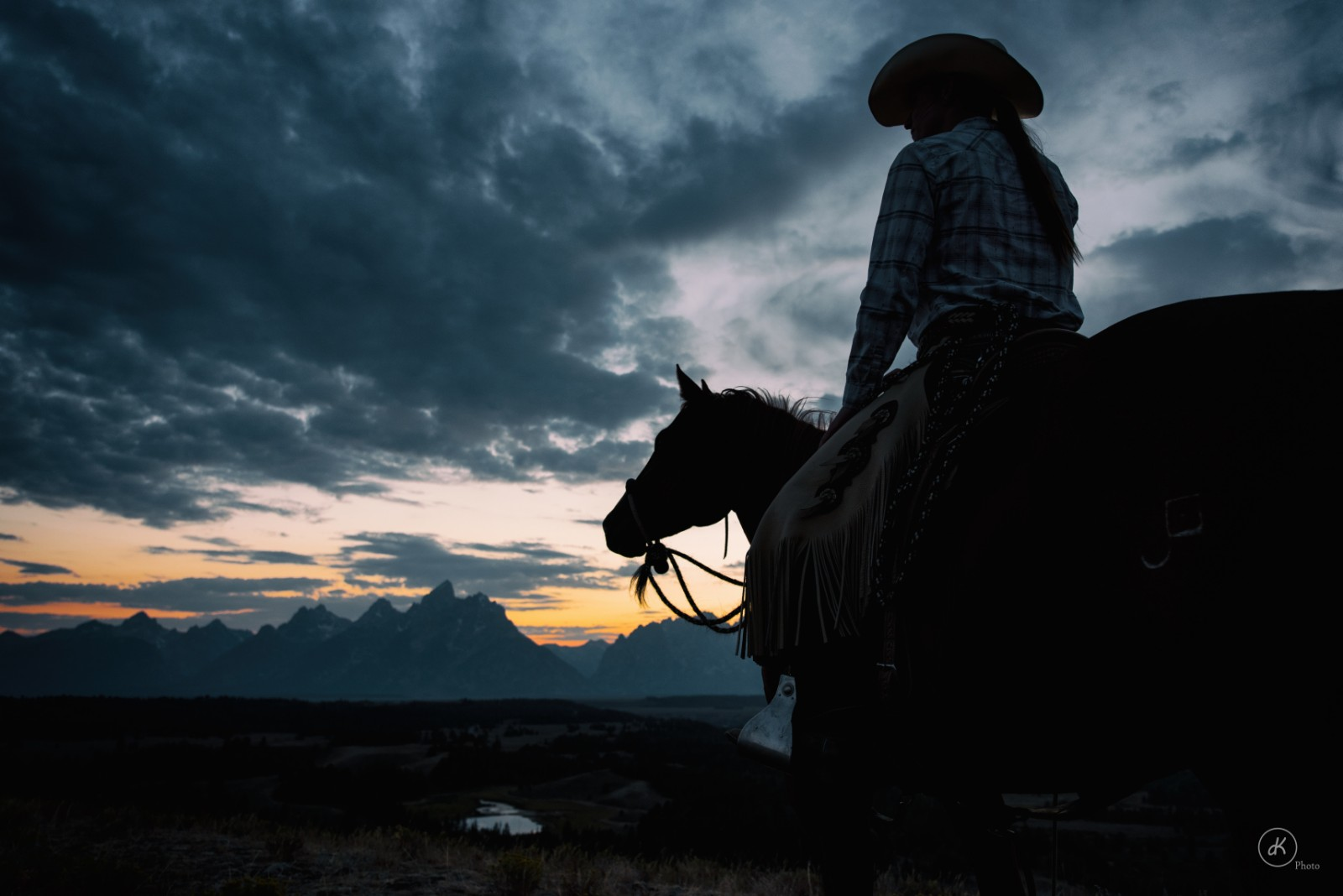 Person riding horse in the shadows at dude ranch with mountains and sunset in background